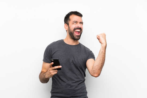 Young handsome man  with phone in victory position