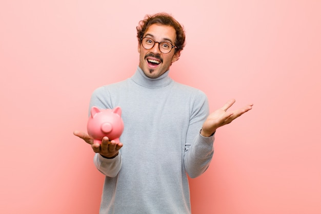 Young handsome man with a piggy bank on pink flat wall
