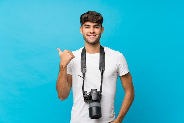 Young handsome man with a professional camera and pointing to the side