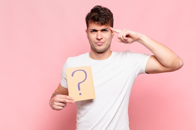Young handsome man with question board