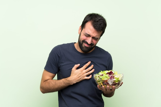 Young handsome man with salad over isolated green wall having a pain in the heart