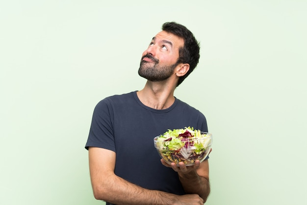 Young handsome man with salad over isolated green wall looking up while smiling