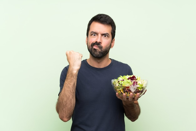 Young handsome man with salad over isolated green wall with angry gesture