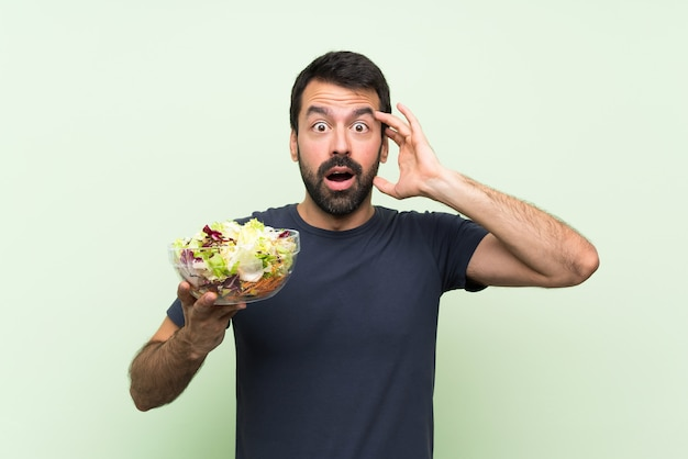 Young handsome man with salad over isolated green wall with surprise expression
