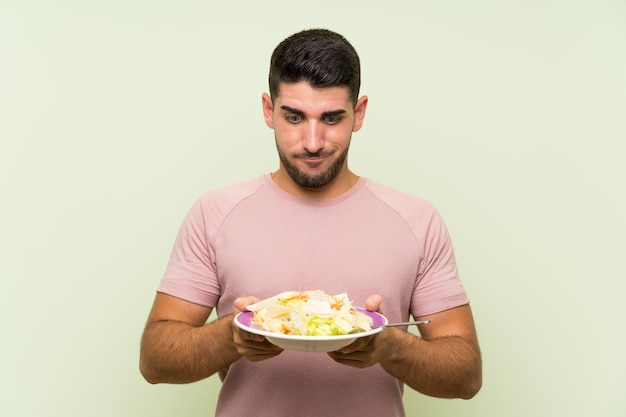 Young handsome man with salad over isolated green wall