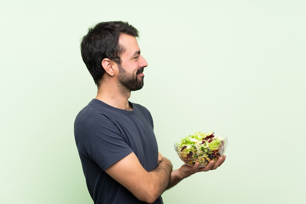 Young handsome man with salad  in lateral position