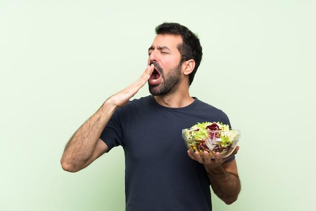 Молодой красавец с салатом на изолированной зеленой стене зевая и прикрывая широко открытый рот рукой