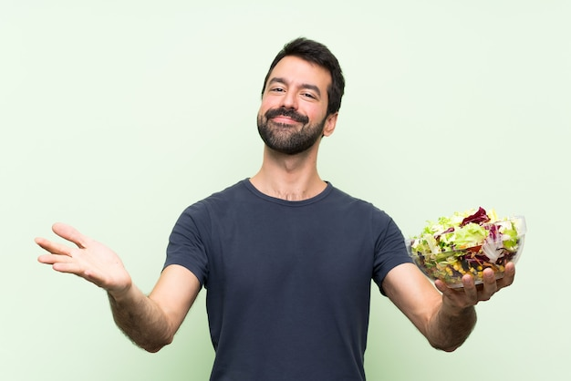 Young handsome man with salad  presenting and inviting to come with hand