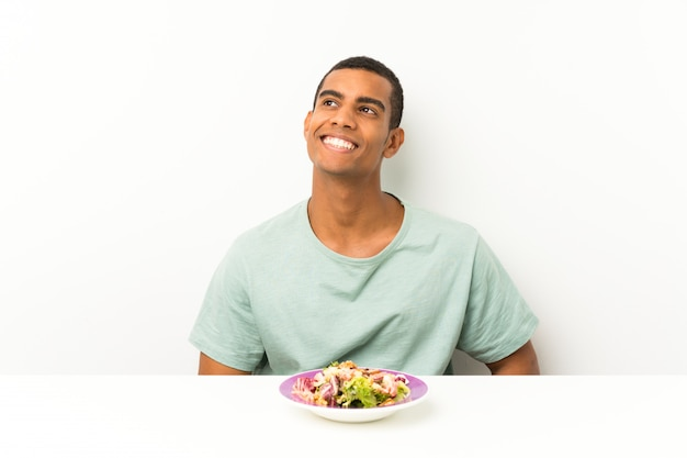 Young handsome man with salad in a table laughing and looking up