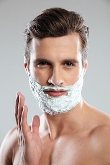 Young handsome man with shaving foam on face