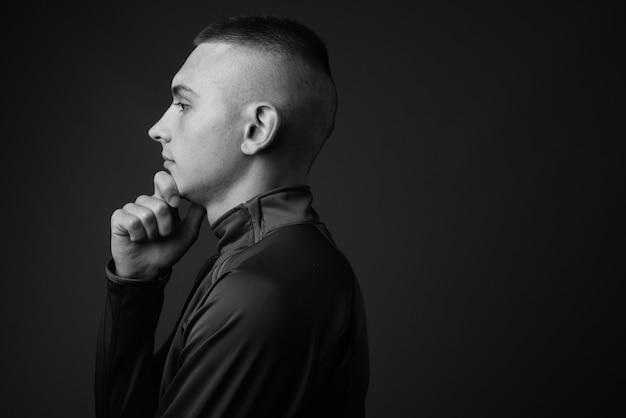 灰色の壁に高い襟のシャツを着ている短い髪の若いハンサムな男。黒と白