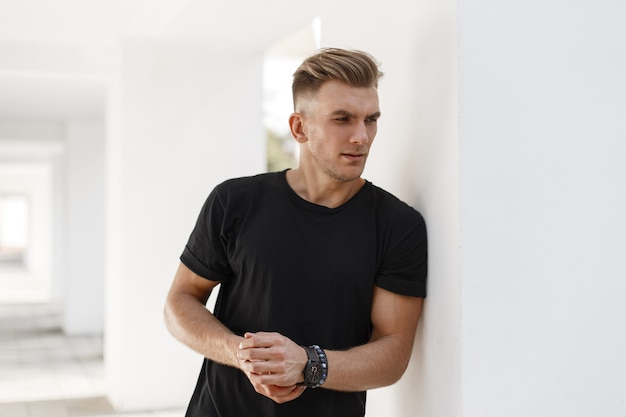 Young handsome man with stylish hairstyle in black t-shirt on the street