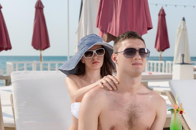 夏に白いラウンジのビーチチェアに座っている間、彼のガールフレンドからリラックスした首のマッサージを受けるサングラスをかけた若いハンサムな男