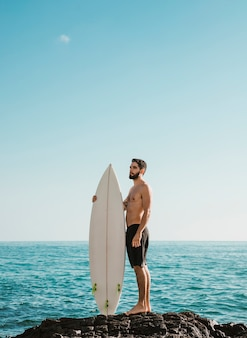 Young handsome man with surf board on stone near sea