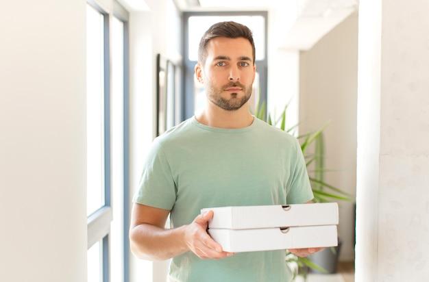집에서 피자 상자를 테이크 아웃하는 젊은 잘 생긴 남자