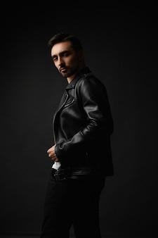 Молодой красавец с небритым лицом в черной кожаной куртке позирует на темном фоне