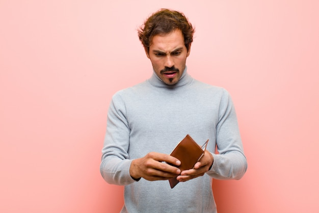 Young handsome man with a wallet against pink flat wall