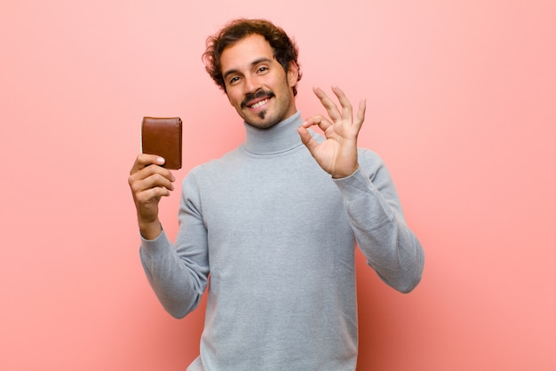 Young handsome man with a wallet  pink flat wall