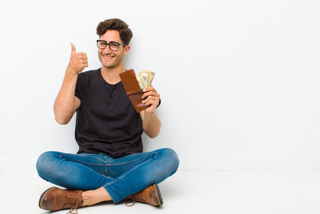 Young handsome man with a wallet sitting on the floor sitting on the floor in a white room