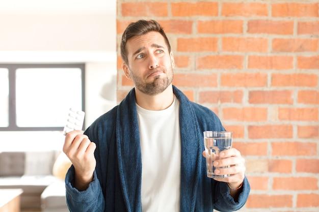 水と錠剤を持つ若いハンサムな男