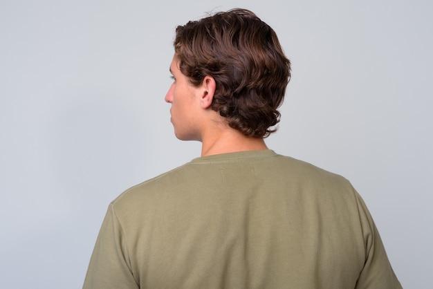 녹색 셔츠를 입고 물결 모양의 머리를 가진 젊은 잘 생긴 남자