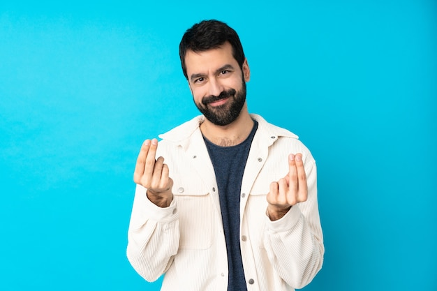 Young handsome man with white corduroy jacket over blue making money gesture