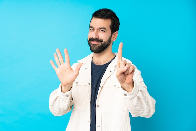 Young handsome man with white corduroy jacket over isolated blue wall counting six with fingers