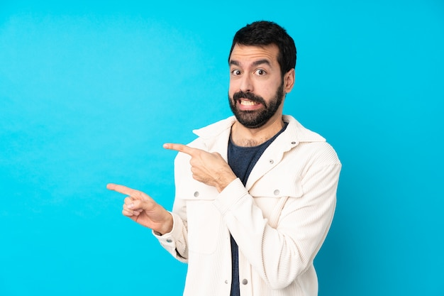 Young handsome man with white corduroy jacket over isolated blue wall frightened and pointing to the side