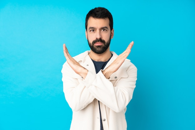 Young handsome man with white corduroy jacket over isolated blue wall making no gesture