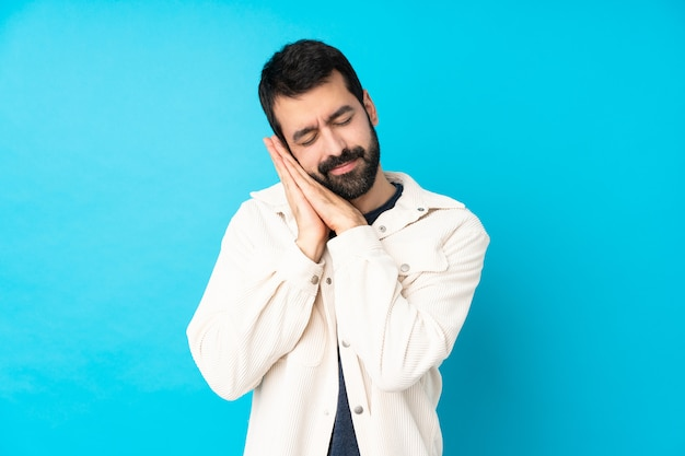 Young handsome man with white corduroy jacket over isolated blue wall making sleep gesture in dorable expression