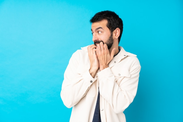 Young handsome man with white corduroy jacket over isolated blue wall nervous and scared putting hands to mouth