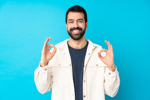 Young handsome man with white corduroy jacket over isolated blue wall showing an ok sign with fingers
