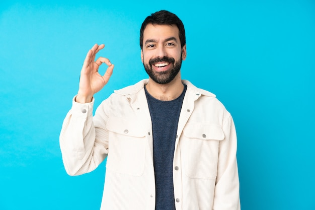 Young handsome man with white corduroy jacket over isolated blue wall surprised and showing ok sign