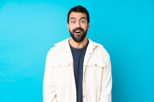 Young handsome man with white corduroy jacket over isolated blue wall with surprise facial expression