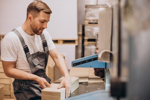 Giovane uomo bello che lavora in una fabbrica