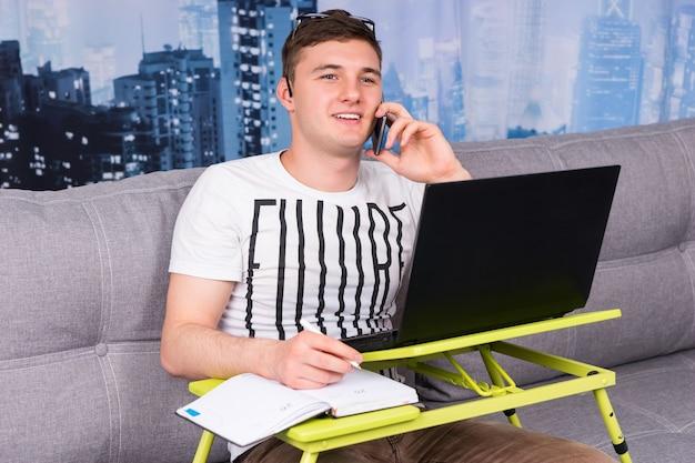 집에서 일하는 젊고 잘생긴 남자는 소파에 앉아 메모를 작성하고 노트북 컴퓨터를 사용하는 동안 휴대 전화로 이야기합니다.
