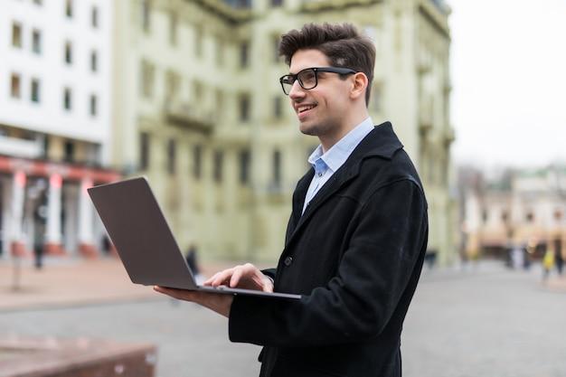 彼のラップトップで屋外で働く若いハンサムな男。