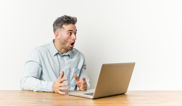 Young handsome man working with his laptop being shocked because of something she has seen.