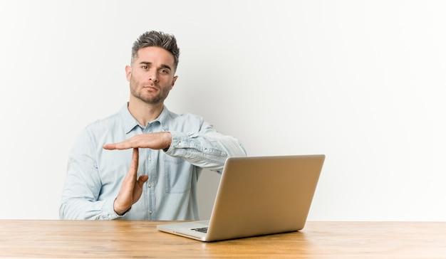 タイムアウトジェスチャーを示す彼のラップトップで作業している若いハンサムな男。