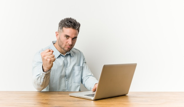 Young handsome man working with his laptop showing fist to camera, aggressive facial expression.