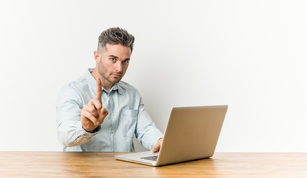 Young handsome man working with his laptop showing number one with finger.