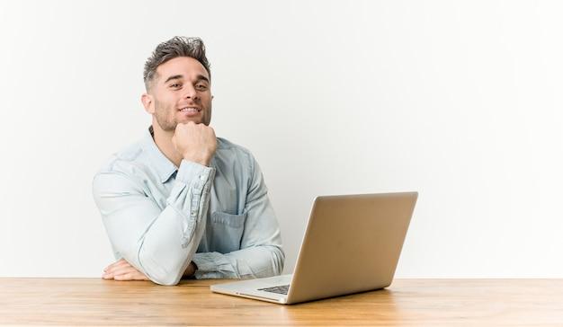 彼のラップトップで作業している若いハンサムな男は、幸せで自信を持って笑って、手であごに触れています。
