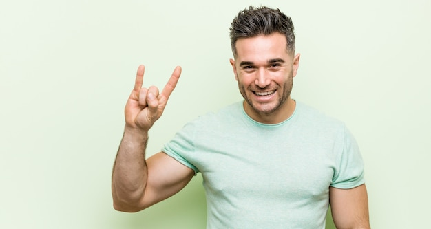 Young handsome manshowing a horns gesture as a revolution concept.
