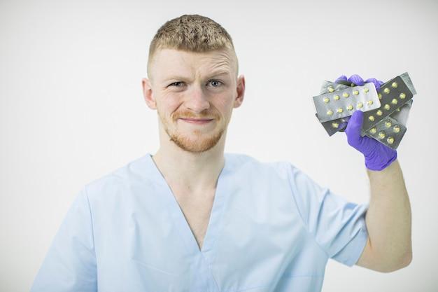 若いハンサムな医療専門家は多くのブリスターピルを持っています
