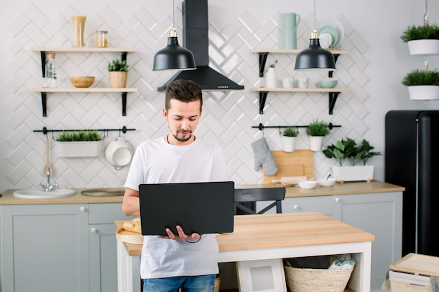 Young handsome men in white t-shirt using laptop while standing near the wooden table at the modern kitchen at home