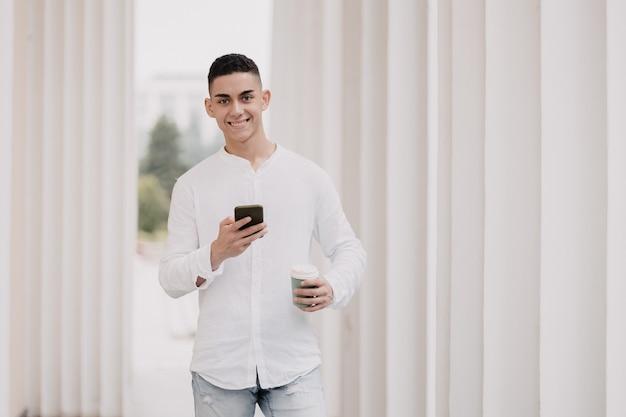 Молодая красивая модель с чашкой кофе и мобильным телефоном. человек улыбается снаружи.