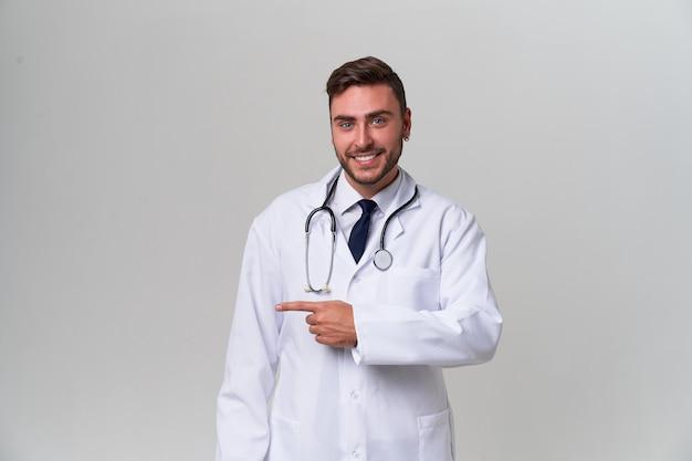 Молодой красивый современный доктор в белой медицинской мантии стоит в студии на белизне. студент-стажер медицинского университета.