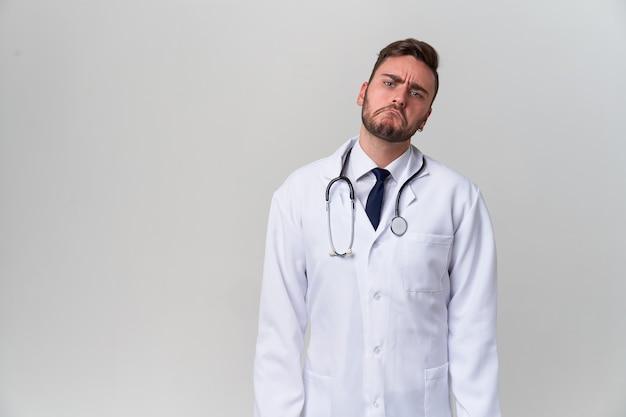 白いスタジオのガウンに白いハンサムな現代医者は立っています。医科大学の学生研修生。