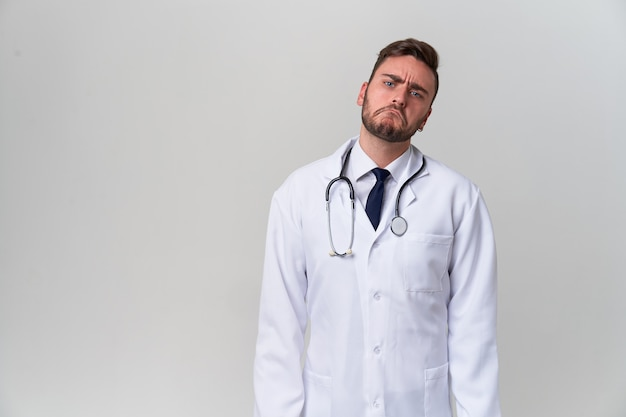Young handsome modern doctor in a white medical gown stands in the studio on a white. student trainee of a medical university.