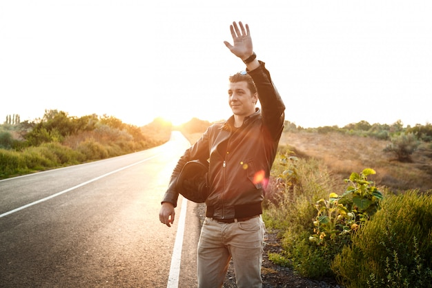 젊은 잘 생긴 motorbiker 인사말, 헬멧을 들고, 시골 도로에서 포즈.